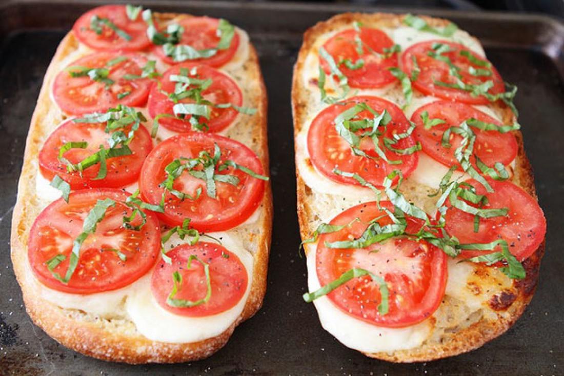 Доставай хлеб из печи. Сверху на сыр выкладывай нарезанные кольцами помидоры. Соли, посыпь перцем и свежей зеленью по вкусу. Снова отправляй в духовку, буквально на минуту