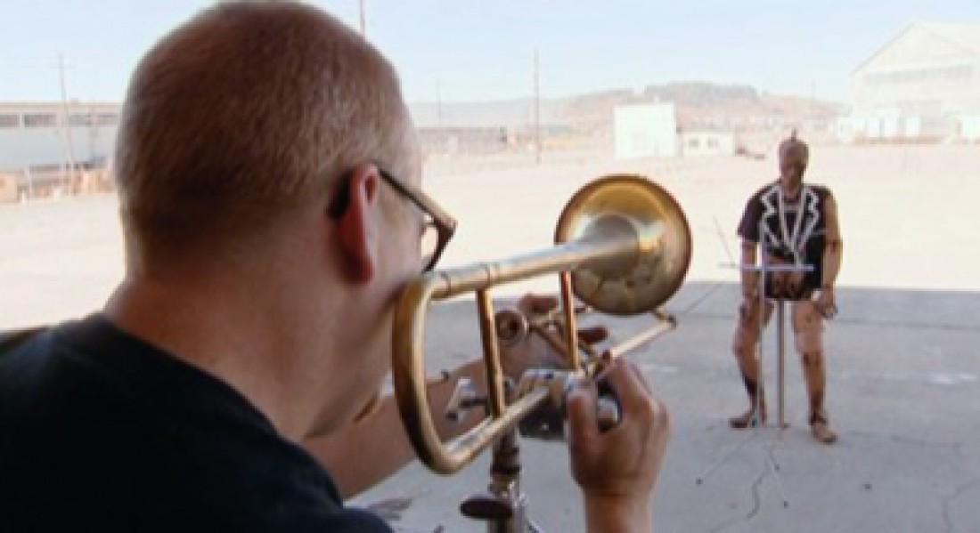 Адам Сэвидж. Целится тромбоном в Бастера