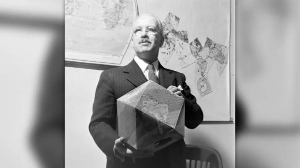 Ричард Бакминстер Фуллер держит собранный многогранный глобус. Обратите внимание на плоскую карту на стене на заднем плане.