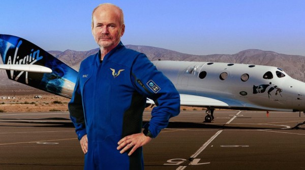 Главный пилот Virgin Galactic Дэйв Маккей показывает свой костюм перед космическим самолетом VSS Unity