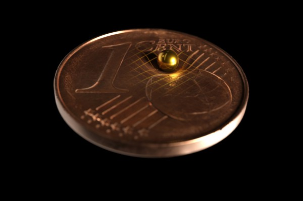 Одна из золотых сфер, использованных в эксперименте, сидит на монете, чтобы показать, насколько она крошечная