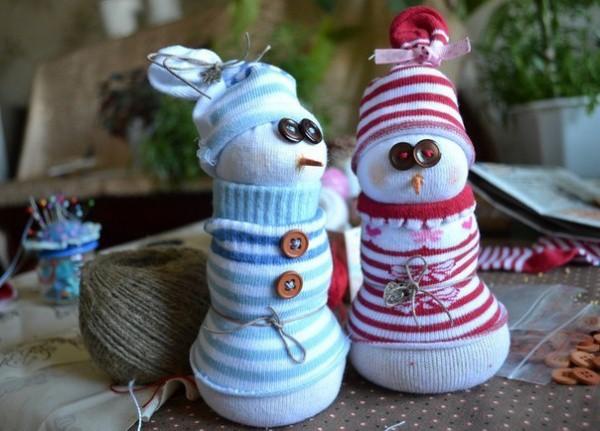Подарки на Новый год своими руками - Снеговики из носка. Тебе понадобится детские белые гольфы (или колготки), носки с цветным рисунком, пшено, стержень от оранжевого карандаша (из него делаем нос-морковку), иголки и нитки, пуговицы.