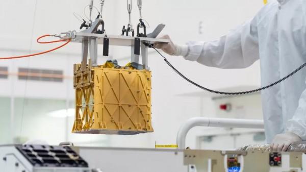 Техники осторожно опускают прибор Mars Oxygen In-situ Resource Utilization Experiment (MOXIE) в брюшко марсохода Perseverance