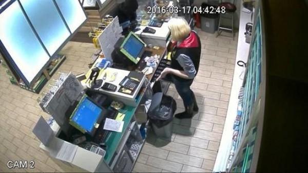 Женщина-кассир отдает преступнику деньги