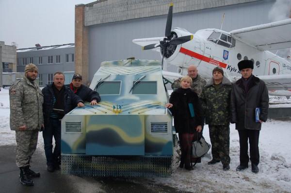 Новый броневик в окружении создателей на фоне легендарного АН-2
