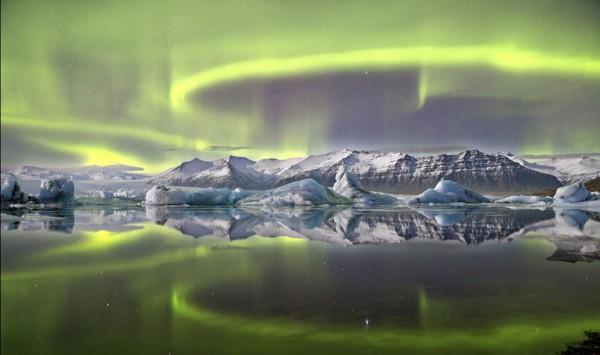 Фотография полярного сияния ярко-зеленого цвета над Исландией и его отражения в леднике заповедника Ватнайокулль британского фотографа Джеймса Вудэнда получила главный приз конкурса