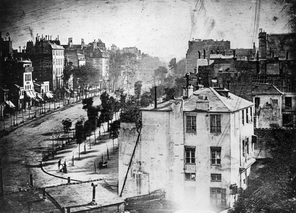 Самое раннее дагеротипное изображение человека, сделанное Дагером. Вид на бульвар дю Тампль в Париже, весна 1838 года (между 24 апреля и 4 мая)[4]. В левом нижнем углу видны чистильщик обуви и его клиент. Все движущиеся фигуры и экипажи из-за длительной выдержки (около 10—12 минут) не отобразились на снимке