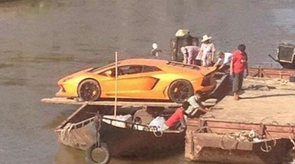 Оранжевый Lamborghini Aventador грузят на лодку