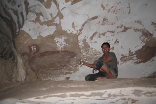 Исследователь Адхи Агус Октавиана с изображением свиньи в пещере Леанг Тедонгнге в Индонезии
