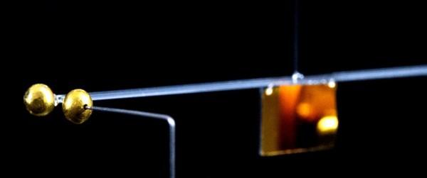 Команда измерила гравитационное притяжение между двумя крошечными золотыми шарами, один на конце стеклянного стержня, подвешенного на проволоке