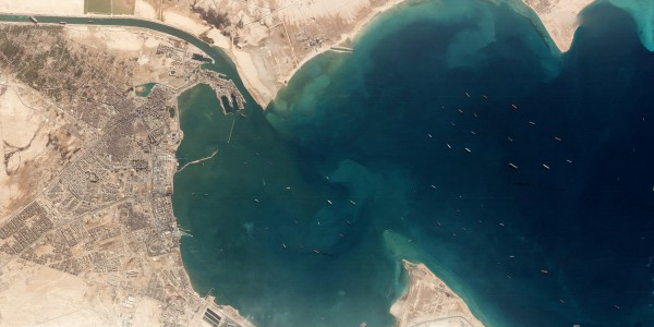 На этой фотографии, сделанной 25 марта одним из космических аппаратов Planet's Dove для визуализации Земли, показан контейнеровоз Ever Given, застрявший в Суэцком канале (вверху слева), и очередь судов, ожидающих входа в канал со стороны Красного моря.