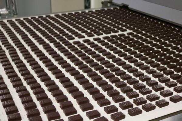 Контролер выискивает повредженые конфеты и удаляет их с конвеера
