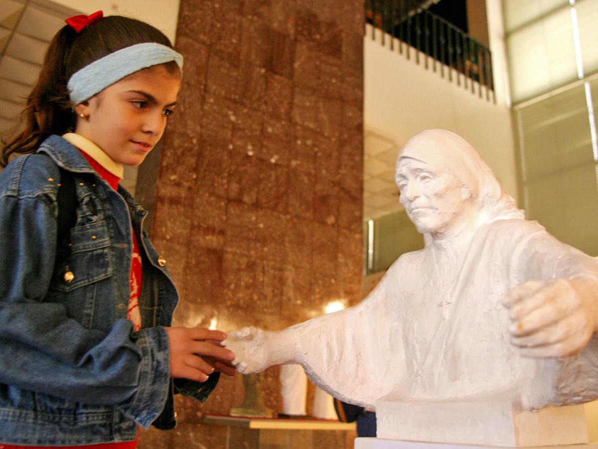 Жизнь в Албании. Девочка возле статуи Марии Терезы в Национальном историческом музее. Родители Матери Терезы были албанцами и к тому же католиками. Сейчас католики составляют около 10% населения страны.