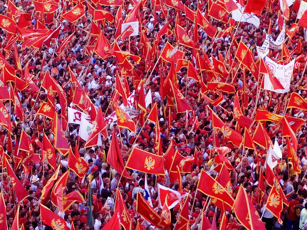 Черногорцы с национальными флагами - двуглавым золотым орлом на красном фоне. 2006 г.