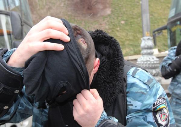 Милиционер показывает травму головы от камня