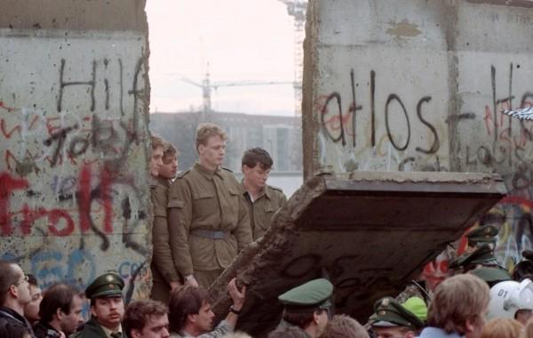 Солдаты ГДР смотрят жителей Берлина, которые разбирают стену