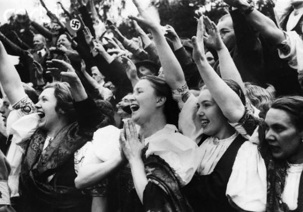 Этнические немцы, одетые в традиционные национальные костюмы отдают нацистский салют, приветствуя Адольфа Гитлера, посетившего Карловы Вары в Судетской области, Чехословакия