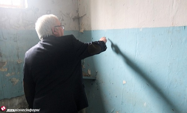 Местный житель показывает надписи в подвале