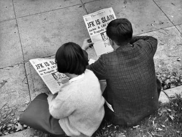 Люди читают новость об убийстве президента.