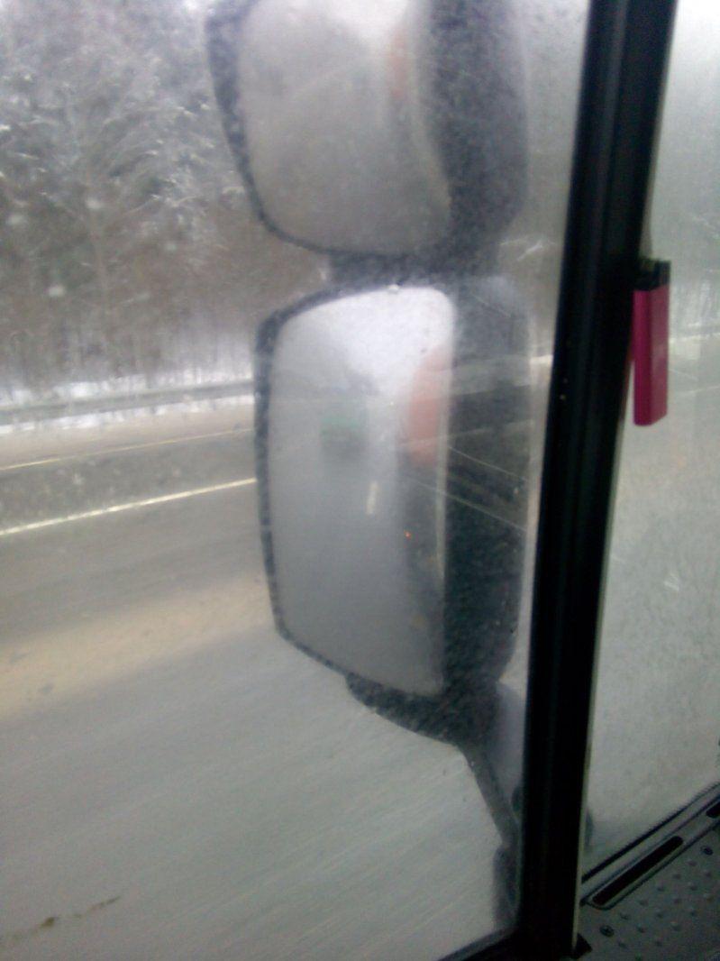 Вид в зеркало заднего вида фуры на легковой автомобиль без включенных фар