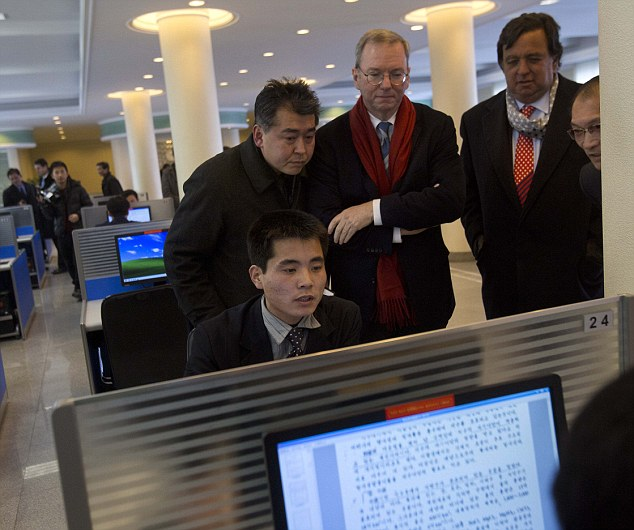 Эрик Шмидт с делегацией наблюдают, как студент пользуется компьютером в универсистетсткой библиотеке