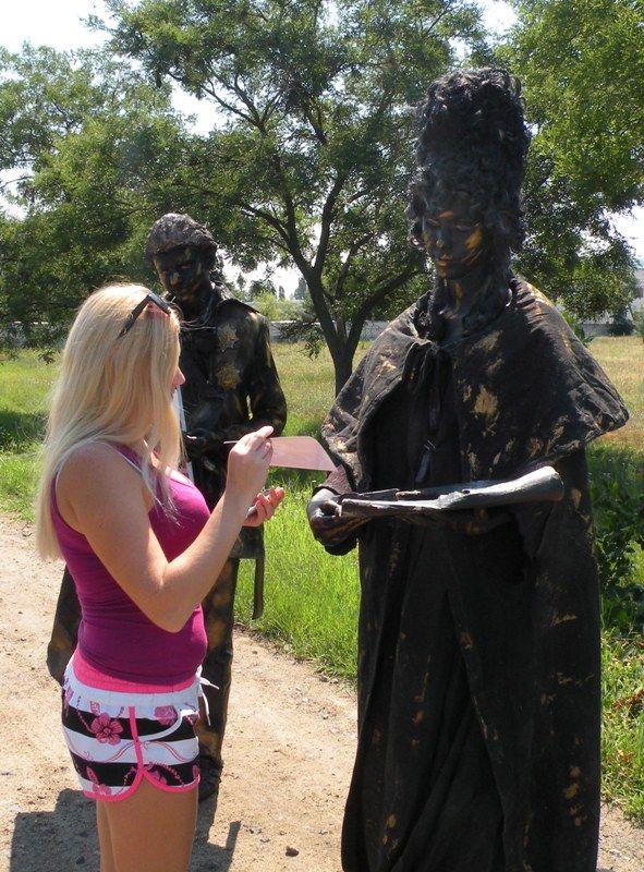 У живых скульптур охотно брали открытки