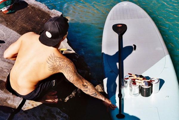 Художник расписывает набережные, балансируя на доске для серфинга