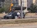 В Киеве экскаватор проломил крышу проезжавшему мимо авто