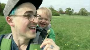 Малыш заразительно смеется из-за одуванчика