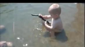 Малыш играет со змеей.