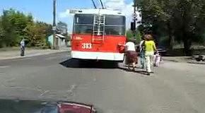 Бабушка толкает троллейбус