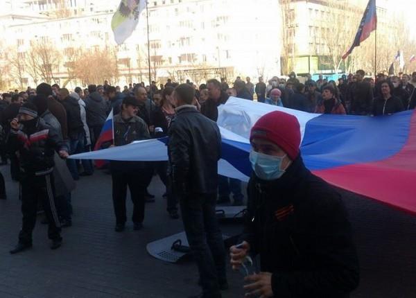 Gens de masques et symboles russes ont battu le cordon de police